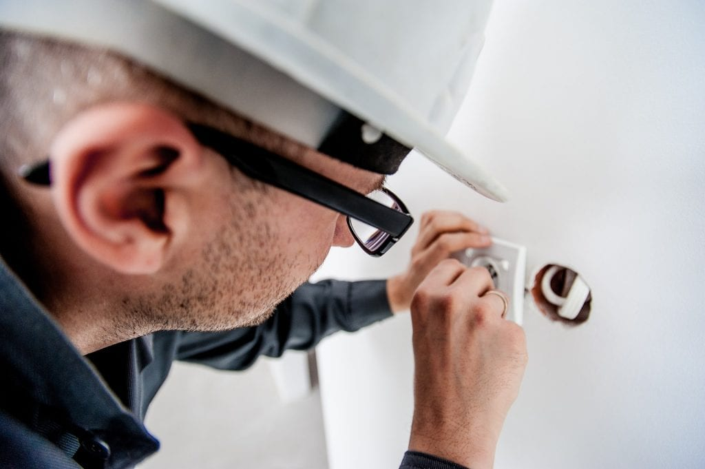 an electrician fitting a new socket into a wall