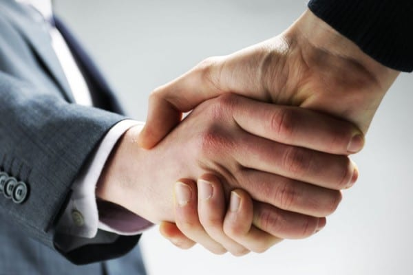 two men shaking hands over a new block management contract